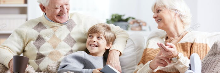 Boy reading a book with grandparents