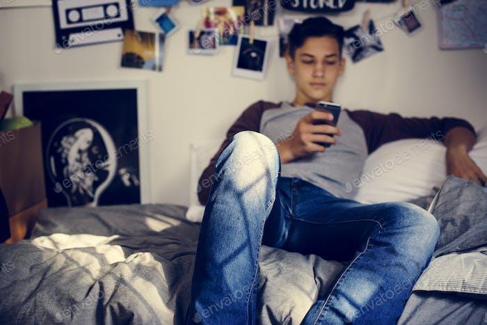 Teenage boy using smartphone in a bedroom social media concept