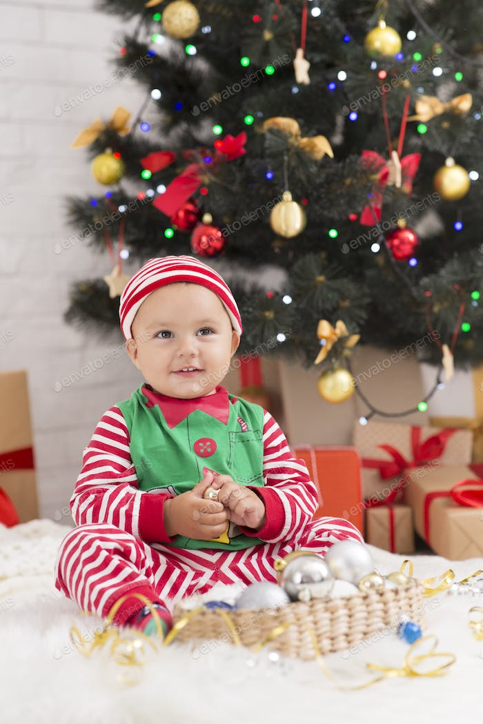 Adorable baby playing with decorations under Xmas tree