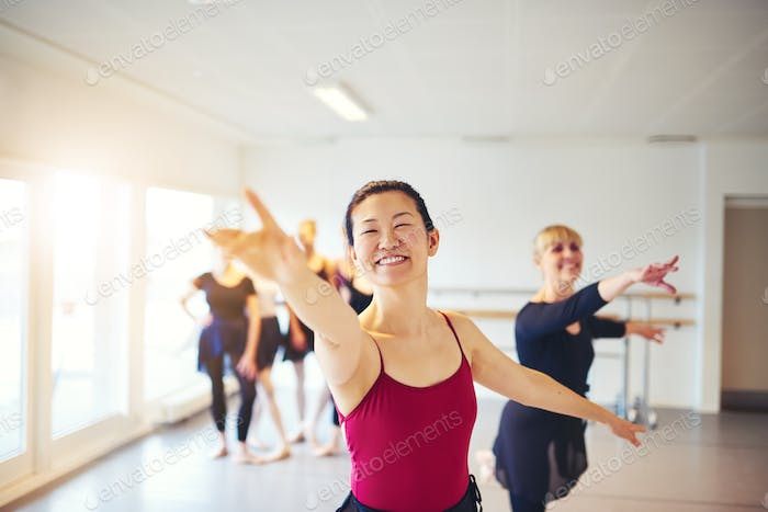 Smiling ballet instructor leading seniors in a ballet class