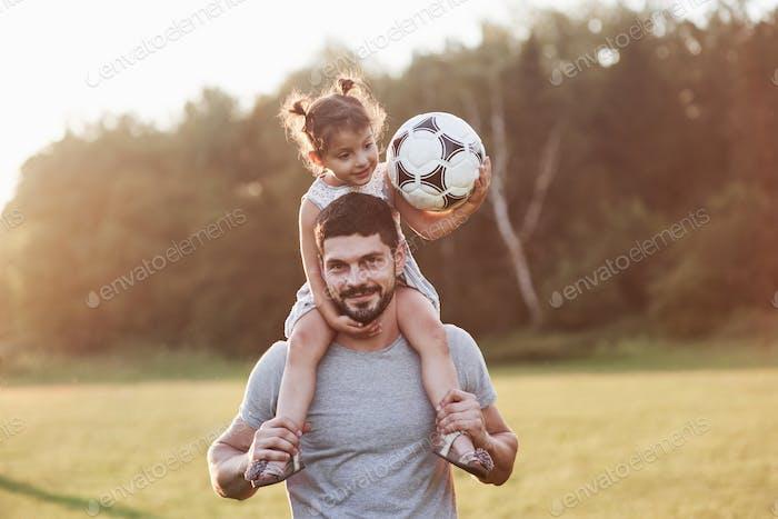 Pures Glück. Foto von Papa mit seiner Tochter auf schönem Gras und Wald im Hintergrund