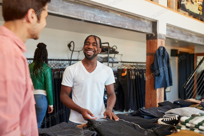 Smiling Sales Assistant Helping Male Customer To Buy Clothes In Fashion Store
