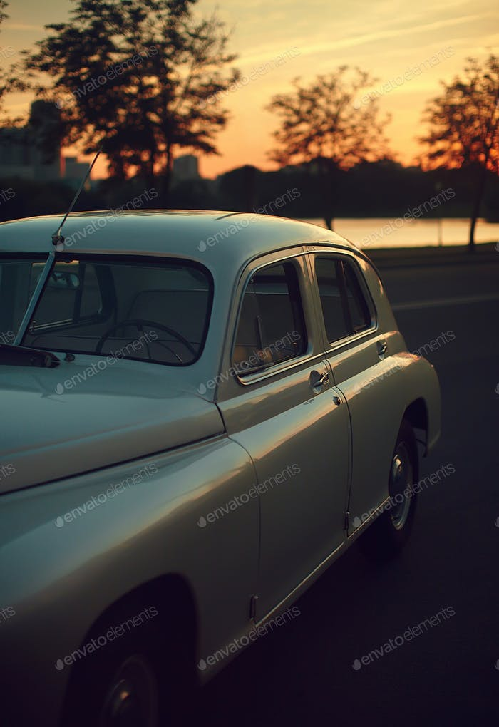 Vintage retro old car in the street behind the sunset in summer