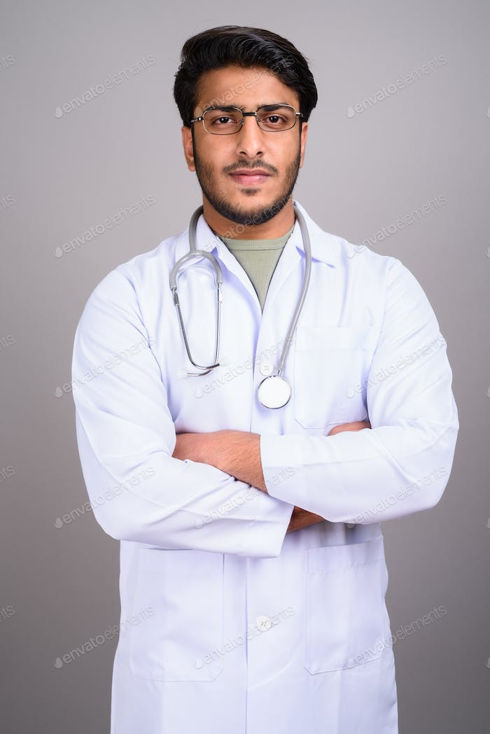 Portrait of Indian man doctor against gray background