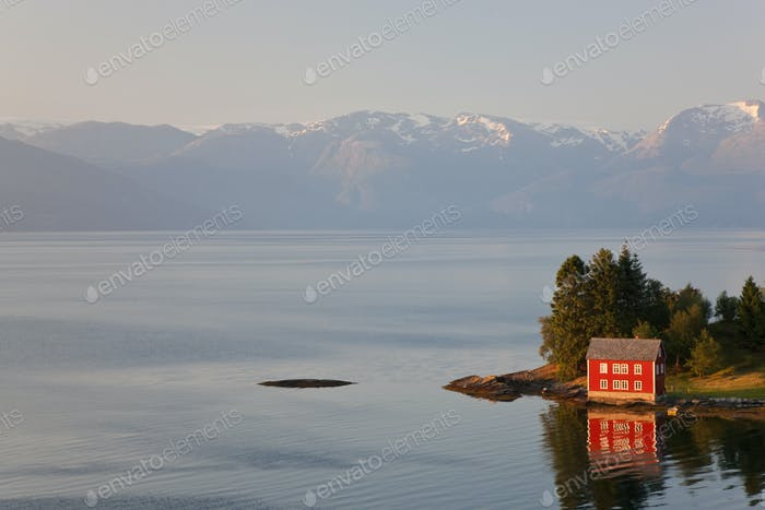 Traditional redwooden house standing on sea shore, snow capped mountains in the distance.