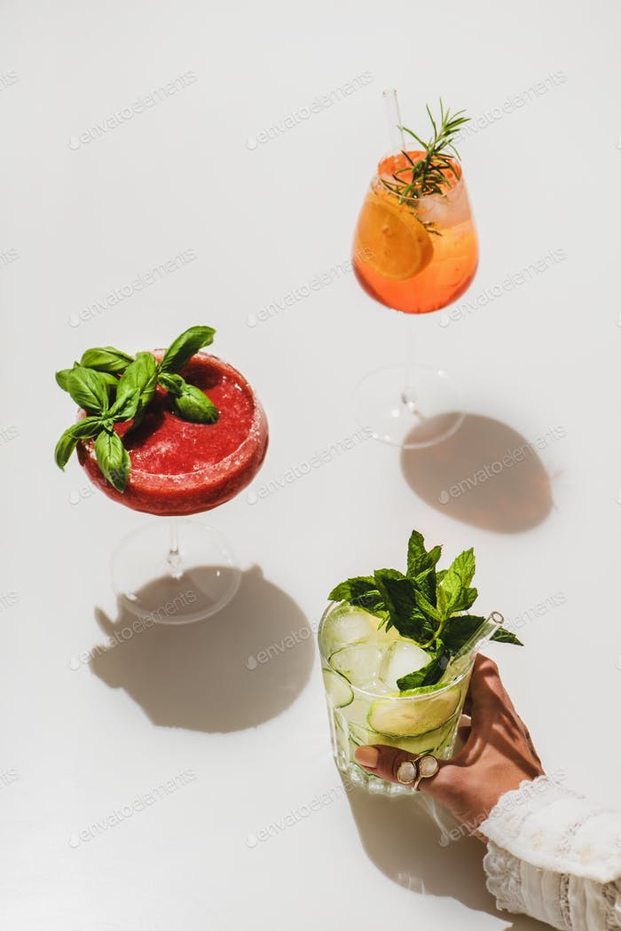 Aperol Spritz, strawberry basil Margarita and Gin-tonic in womans hand