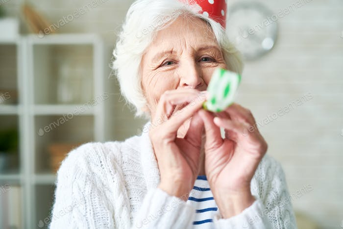 Carefree granny blowing party horn