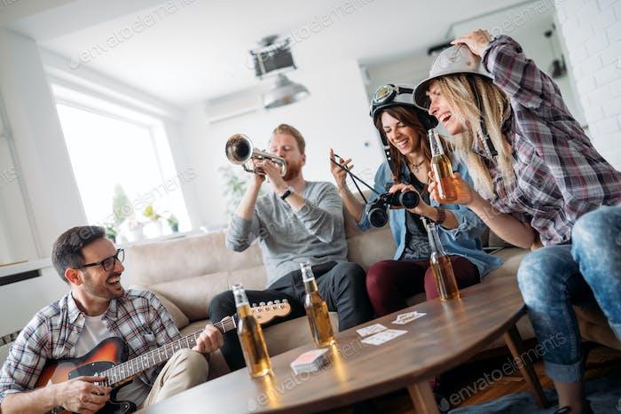 Glückliche Gruppe von Freunden spielen Instrumente und Party
