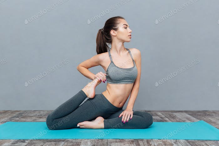 Young woman doing yoga exercise one legged king pigeon