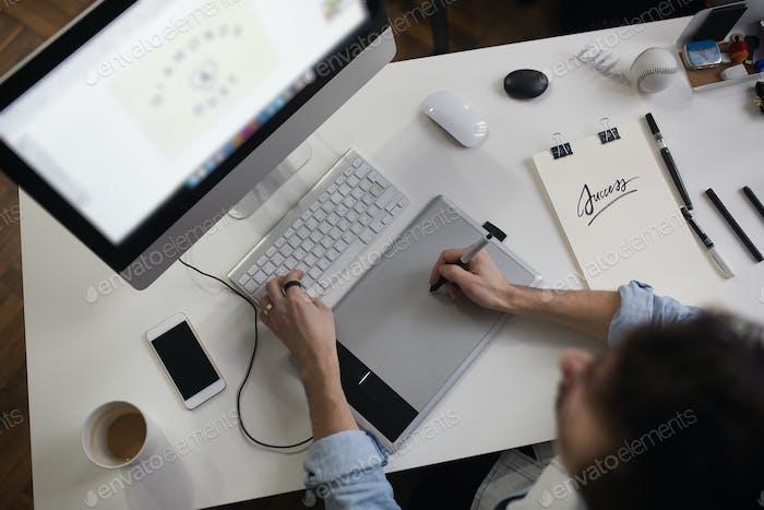 Junge männliche Designer mit Grafiken ablett während der Arbeit mit com