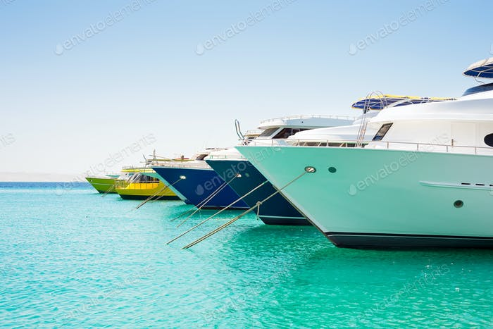 Anchored big yachts and sailboats on a turquoise water