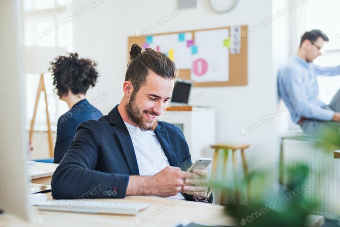 A portrait of young businessman with smartphone and colleagues in a modern office.