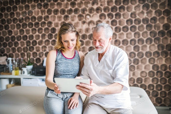 Senior male physiotherapist and young woman with tablet sitting.
