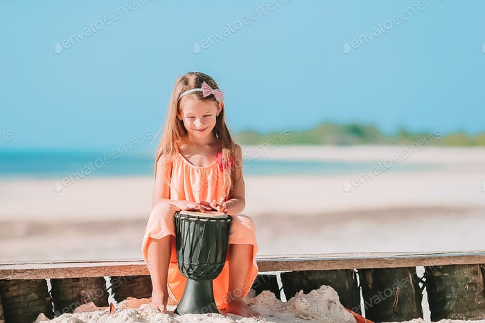 Little happy girl playing on african drums.