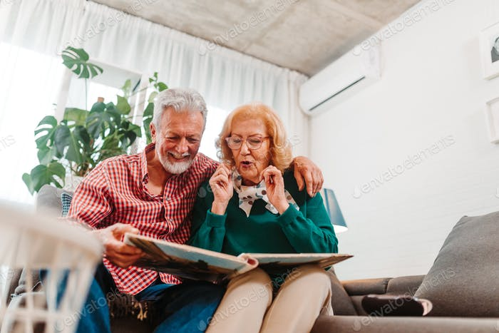 Happy couple looking at old family photos. Happy memories are everything.