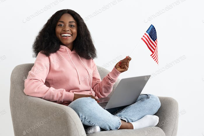 Black lady with laptop and american flag in arm chair