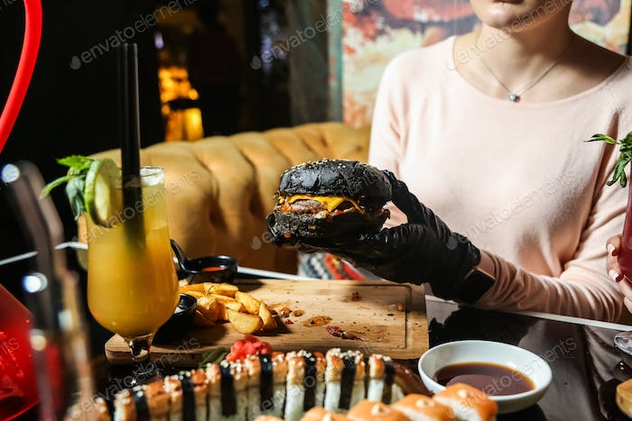 side view woman eating black meat burger with mix sushi rolls and soy sauce on the table