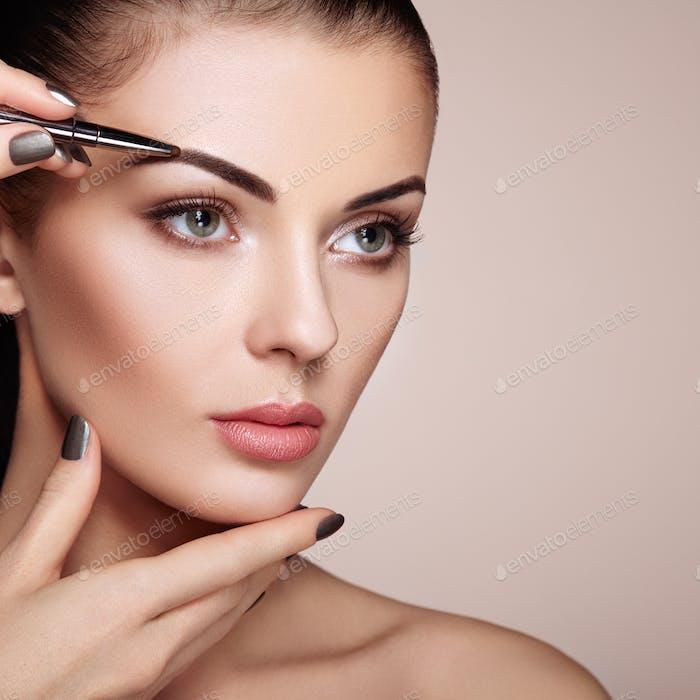 Schöne Brünette Frau malt die Augenbrauen