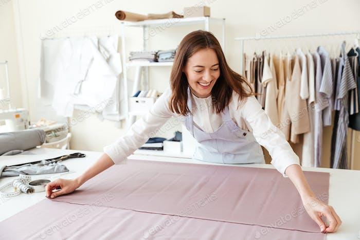 Woman seamstress spreading fabrics in workshop