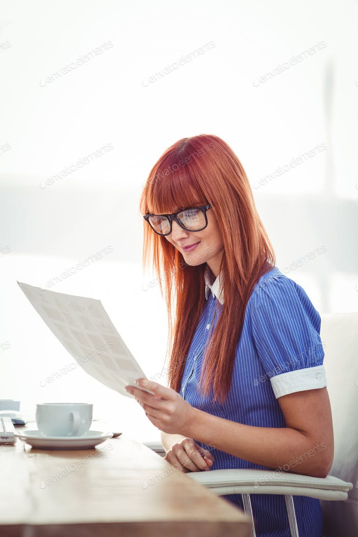 Smiling hipster woman looking at document in her office