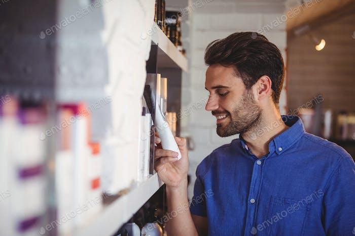 Male hair dresser selecting shampoo from shelf