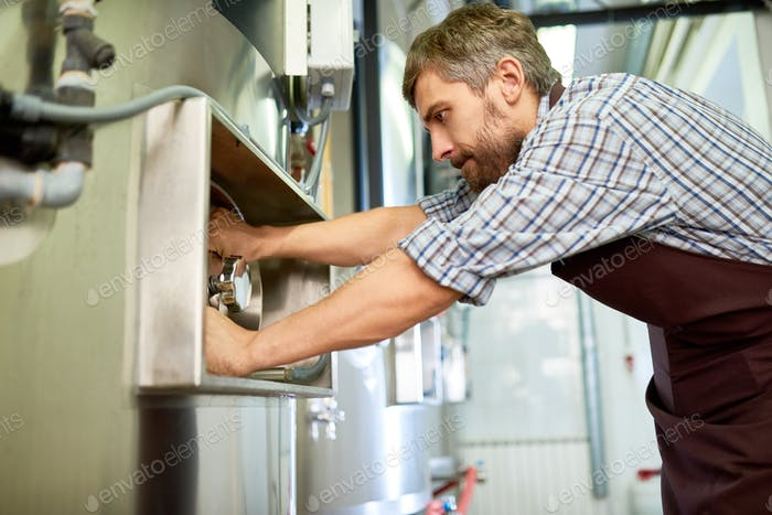 Busy skilled maintenance technician repairing brewery equipment