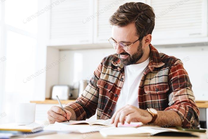 Porträt von aufgeregten bärtigen Mann lächelnd während der Arbeit zu Hause