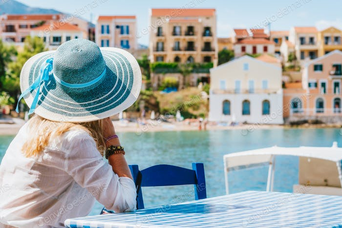 Rear view of tourist woman sitting cafe wear blue sunhat admire colorful tranquil houses of Assos