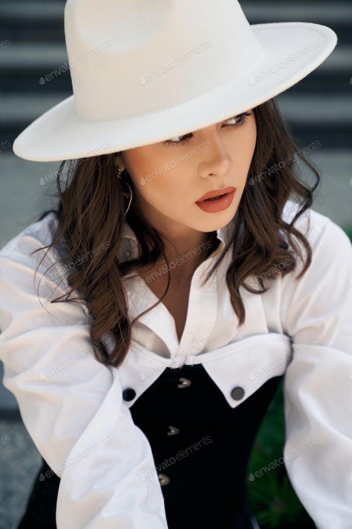 Gorgeous model wearing hat posing outdoors