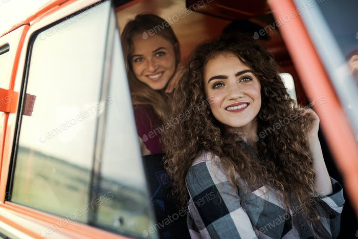 Young female friends on a roadtrip through countryside, looking out of minivan.