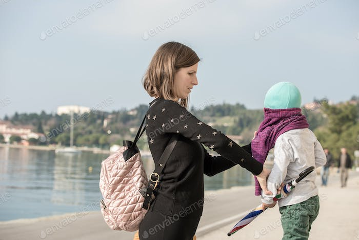 Young mother dressing her son in a pullover