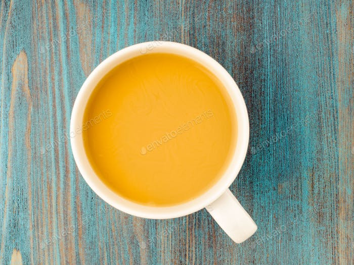 large white mug of tea with milk on a wooden blue background, a traditional English drink.