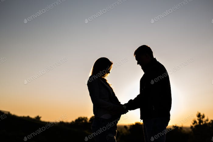 Silhouette of a pregnant woman with husband in sunset