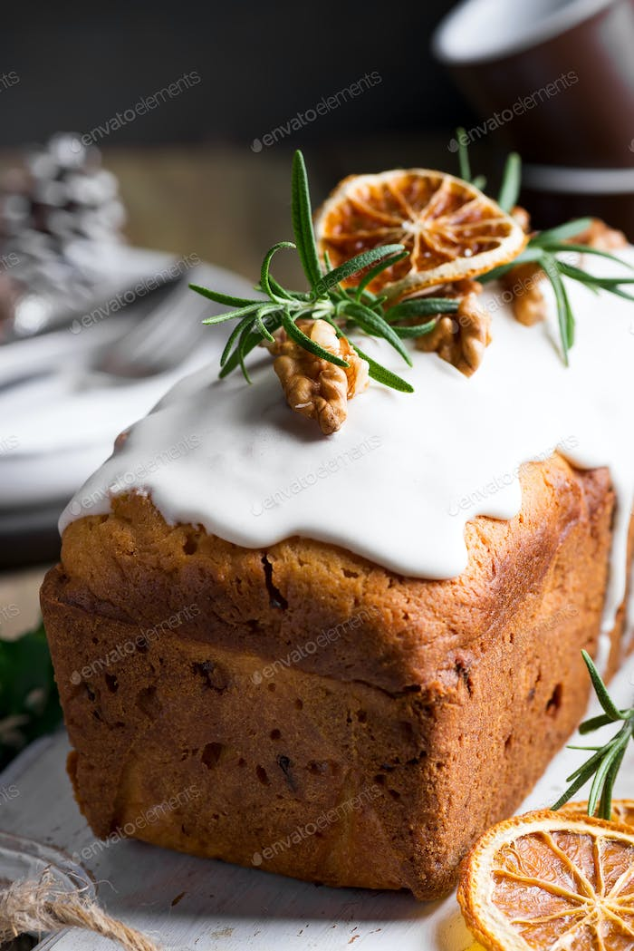 Fruit cake dusted with icing, nuts and dry orange close-up. Christmas and Winter Holidays homemade