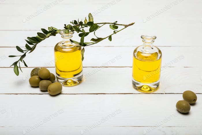 Close-up view of pure olive oil and green olives on wooden surface