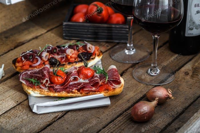Tapas auf knusprigem Brot mit Rotwein