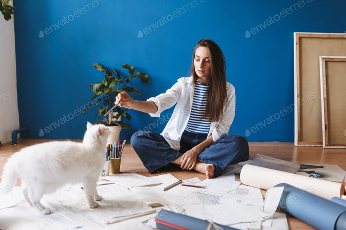 Thoughtful girl sitting on floor with drawings dreamily looking