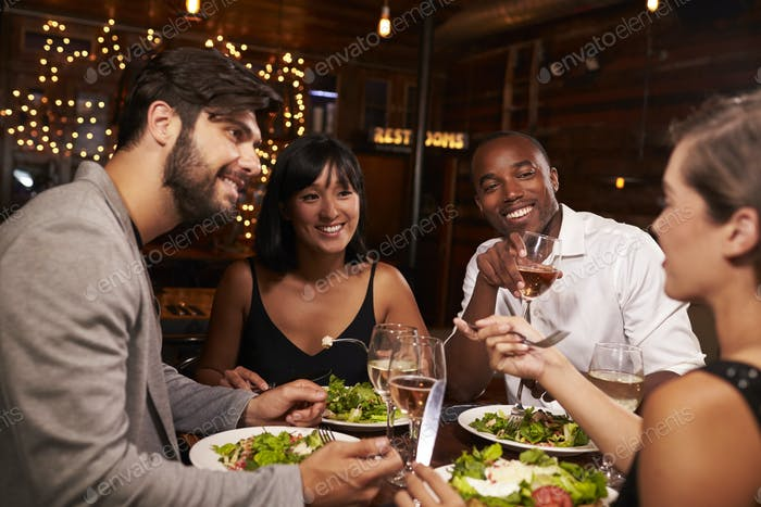 Four friends enjoying dinner and drinks at a restaurant