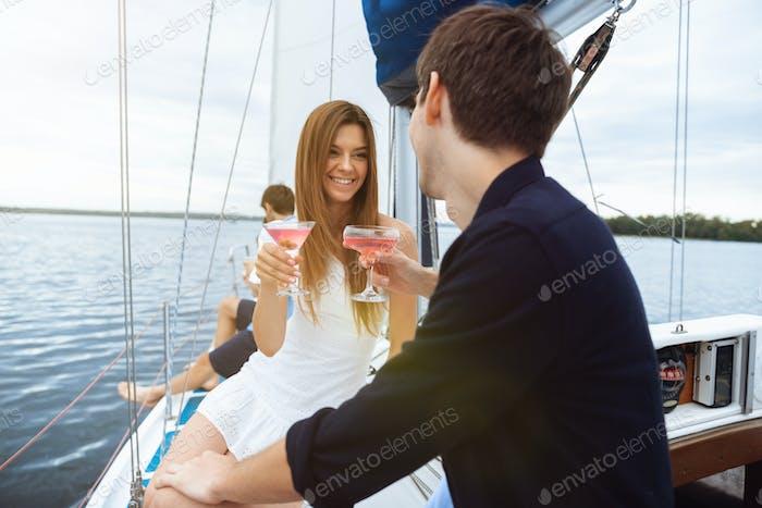 Glückliches Paar trinken Wodka Cocktails auf Boot-Party im Freien, fröhlich und glücklich