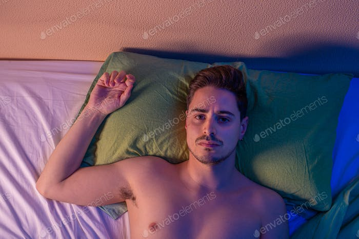 Portrait of a man on the bed from above at night