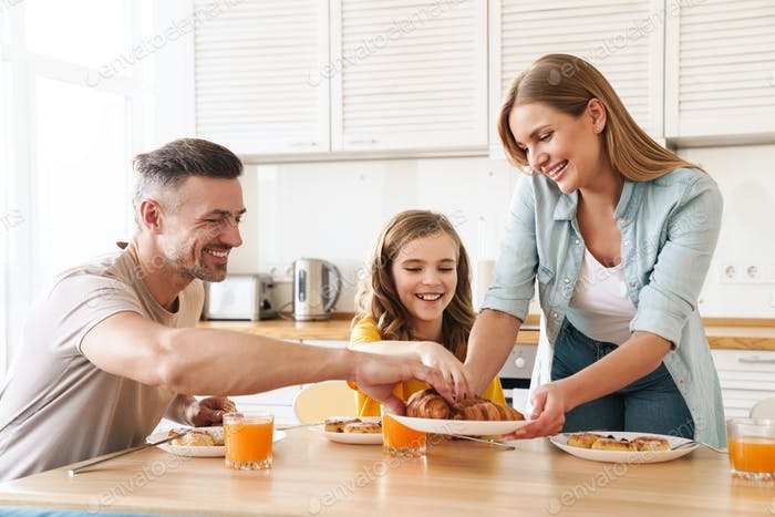 Photo of happy family eating croissants while having breakfast