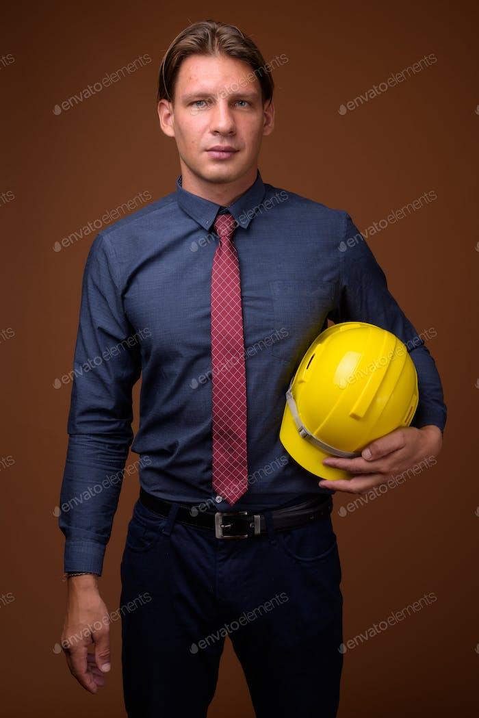 Geschäftsmann mit Hardhat vor braunem Hintergrund