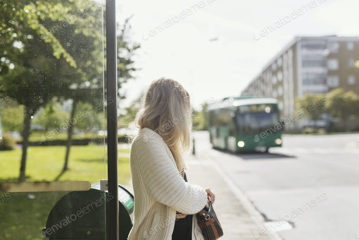 Young woman carrying shoulder bag standing near garbage bin looking at bus
