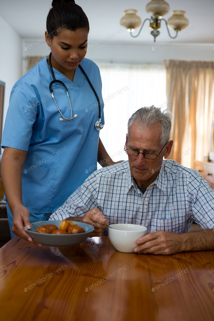 Doctor serving food to senior man at table in nursing home