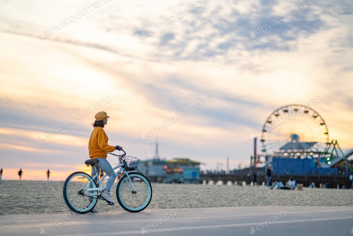 Young woman with bike on the beach in Los Angeles