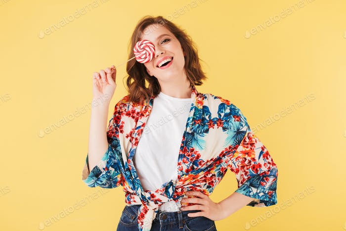 Pretty cheerful lady in colorful shirt standing and covering her face with lollipop candy
