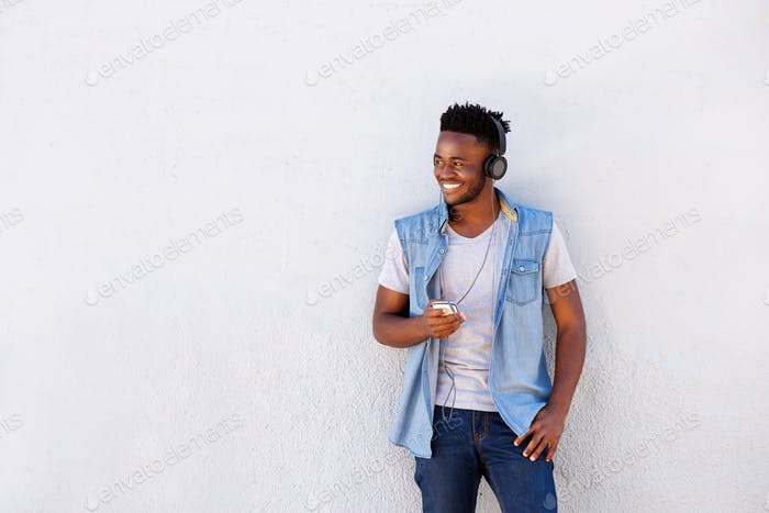 smiling man with headphones and cellphone standing by white wall