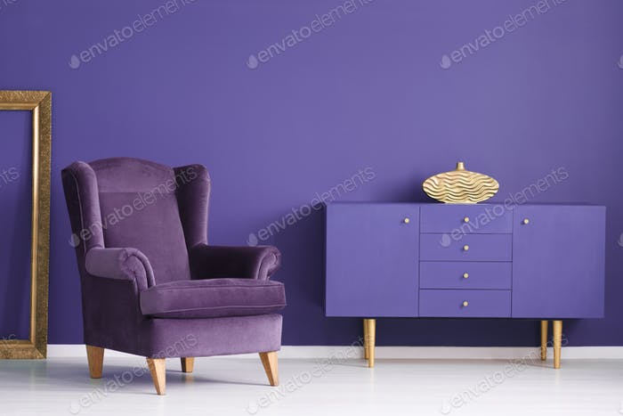 Purple cabinet with a golden vase, comfy armchair and frame in a