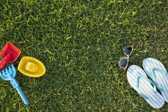 Light Blue Flip Flops, Sunglasses and Plastic Colourful Toys for Children on a Grass