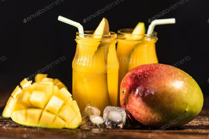 Mango juice and mango on wood table
